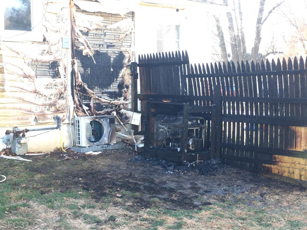 A generator caught fire on the exterior of a house.