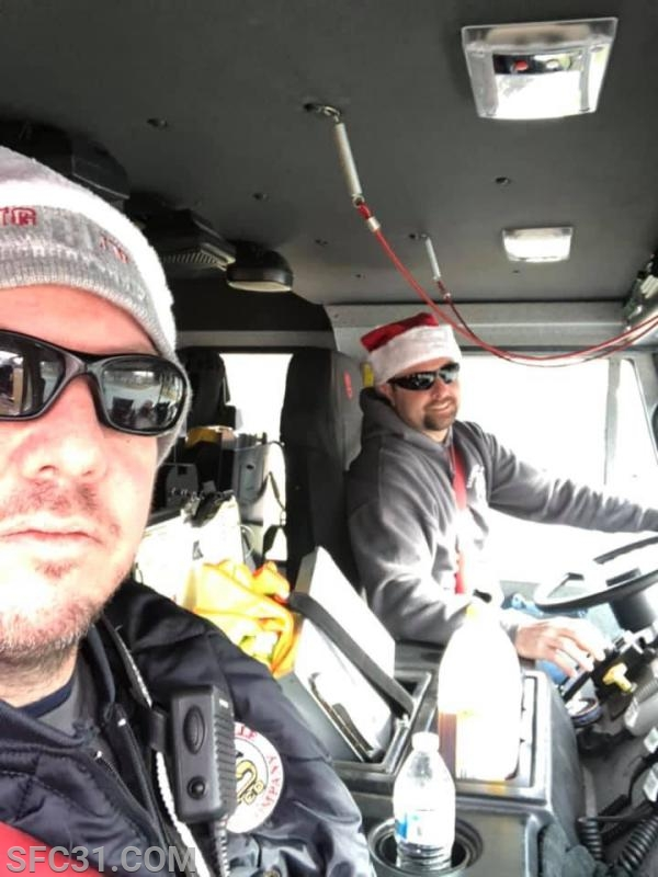 Chief Engineer Conover and Fire Police Captain Rust escort Santa on Engine 31-1.