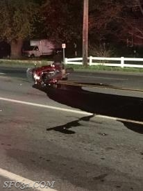One motorcycle on its side after colliding with a passenger car.