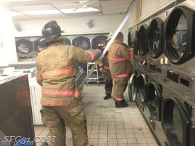 Sadsburyville firefighters extinguish a building fire at the Blue Spot Laundry Mat.