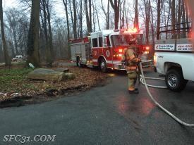 Firefighter/EMT Sly returns the hose line to Engine 31-1.