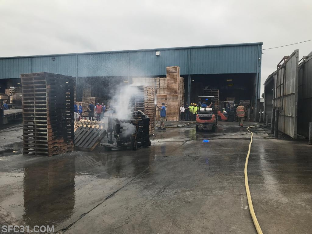 Pallets were pulled out of the building still smoldering.