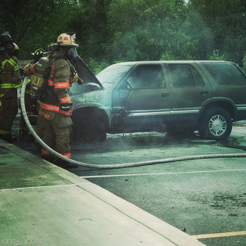 Deputy Chief Brecht knocks down the flames coming from an automobile adjacent to a building.