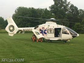 Firefighters load a patient into a helicopter to be transported to a local trauma center for additional care.